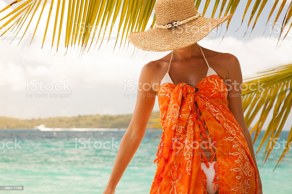unrecognizable woman poses on a tropical Caribbean beach unrecognizable woman in big straw hat, white bikini and orange sarong poses on a tropical Caribbean beach 2015 Stock Photo