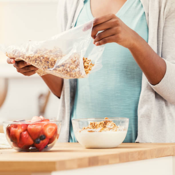 femme méconnaissable verse des céréales de petit déjeuner avec des fruits - en fibre photos et images de collection