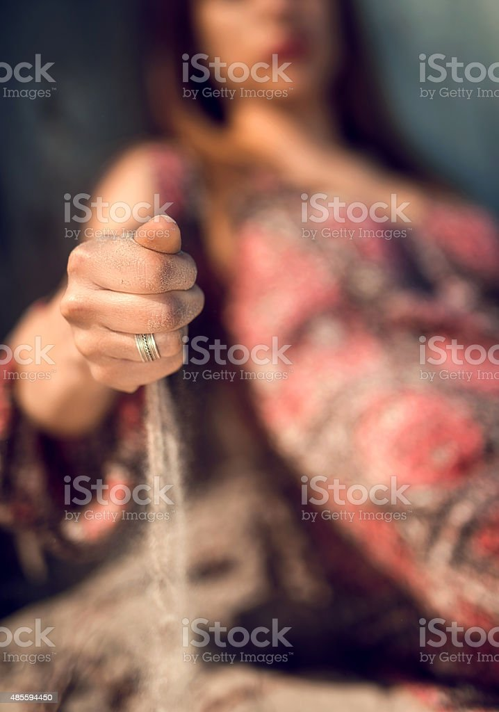 Unrecognizable woman pouting sand from her hand. stock photo