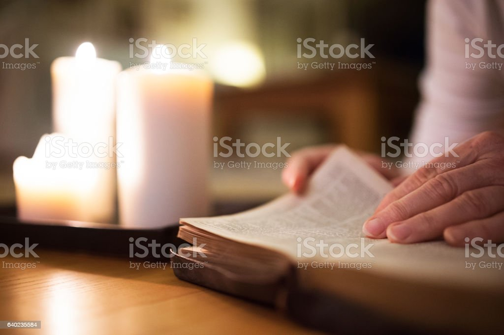 Unrecognizable woman reading Bible. Burning candles next to her. stock photo