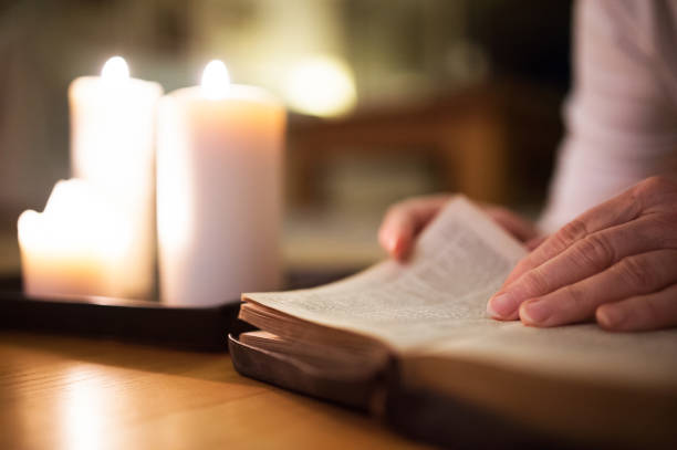 Unrecognizable woman reading Bible. Burning candles next to her. - foto de stock