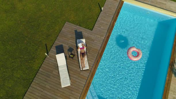 antenne: unkenntlich frau liest beim sonnenbaden am glitzernden pool. - der geheime garten stock-fotos und bilder