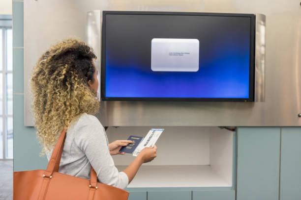 nicht erkennbare frau liest anweisungen auf flughafen-monitor - flugticket vergleich stock-fotos und bilder