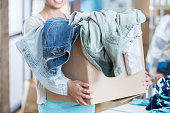 Unrecognizable woman receives box of clothing during clothing drive