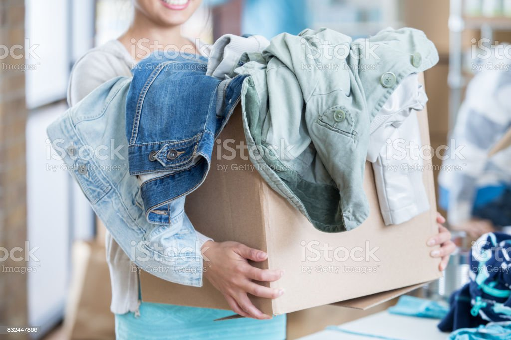 Unrecognizable woman receives box of clothing during clothing drive stock photo
