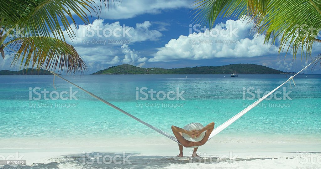 unrecognizable woman relaxing in a hammock at a Caribbean beach stock photo