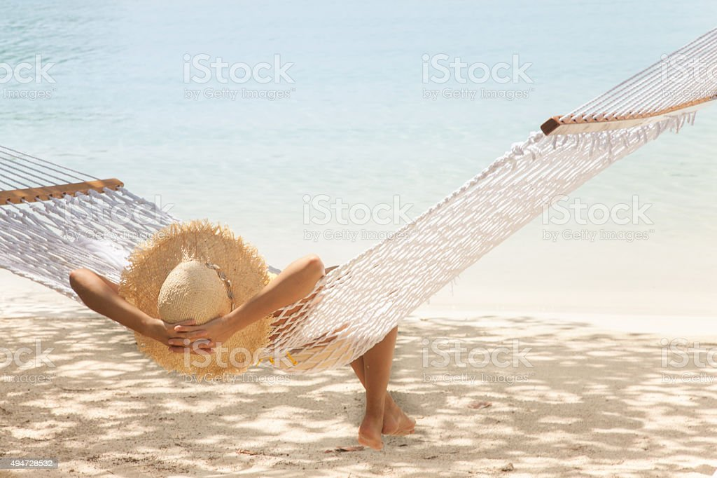 unrecognizable woman relaxing in the hammock at a Caribbean beach stock photo