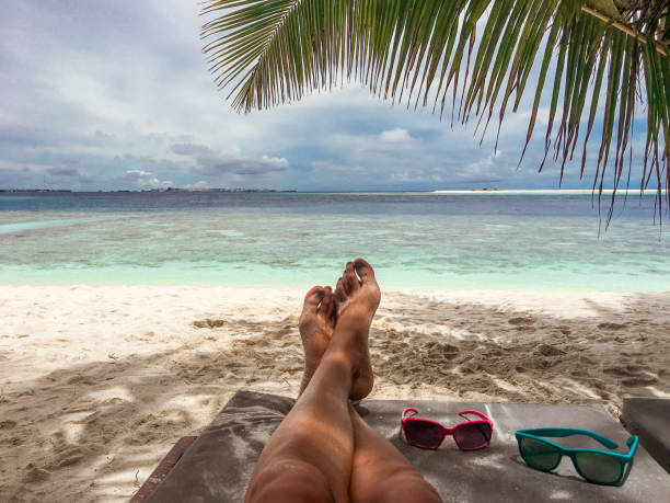 unrecognizable woman relaxing on a tropical beach - woman leg beach pov stock photos and pictures