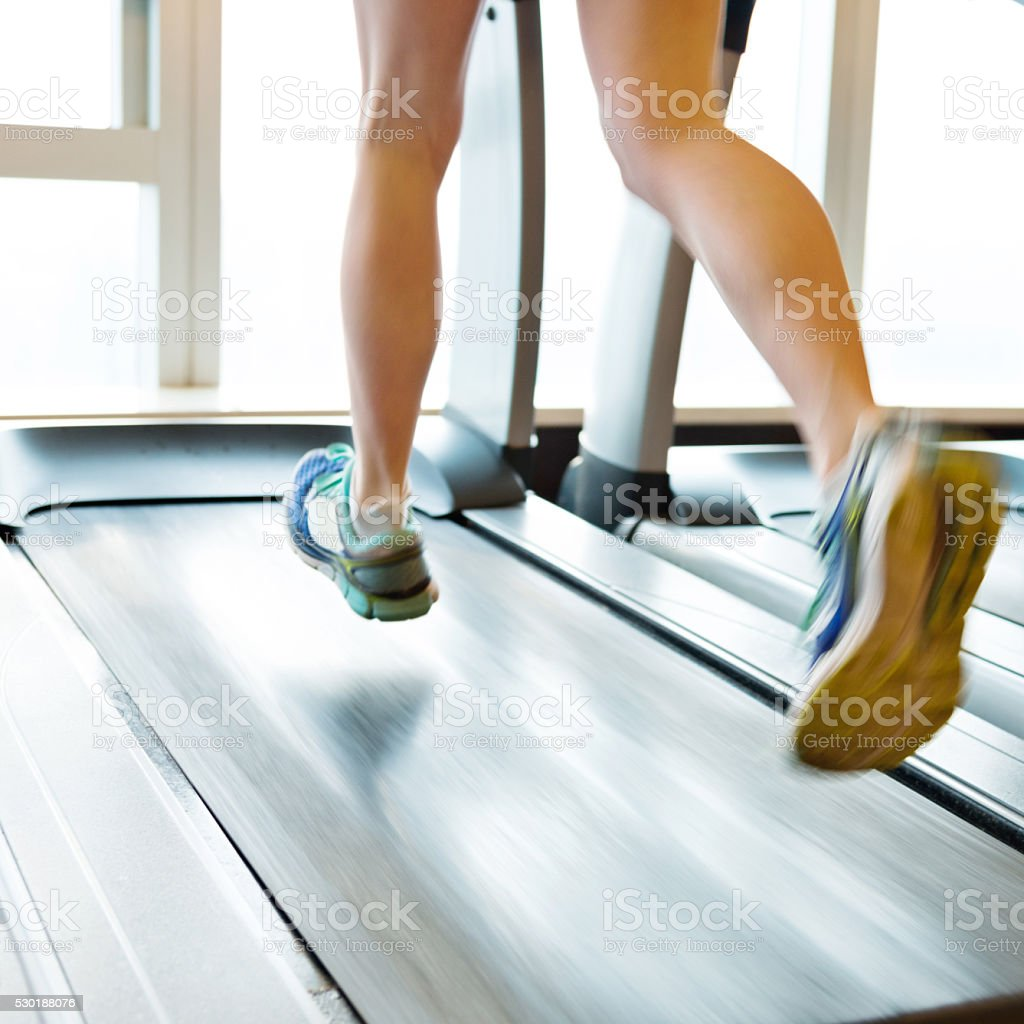 Unrecognizable woman running on treadmills stock photo