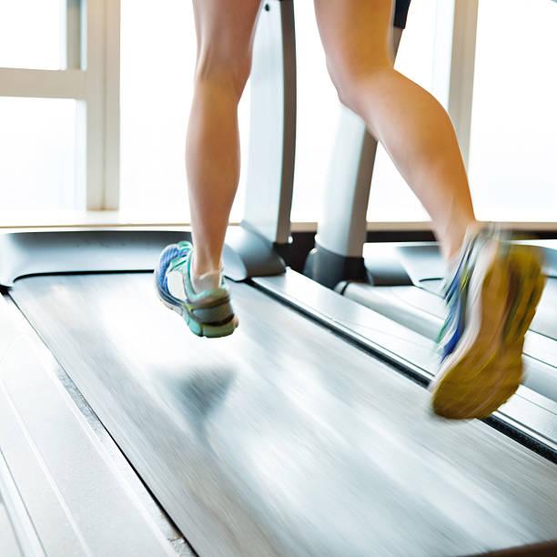 Unrecognizable woman running on treadmills stock photo