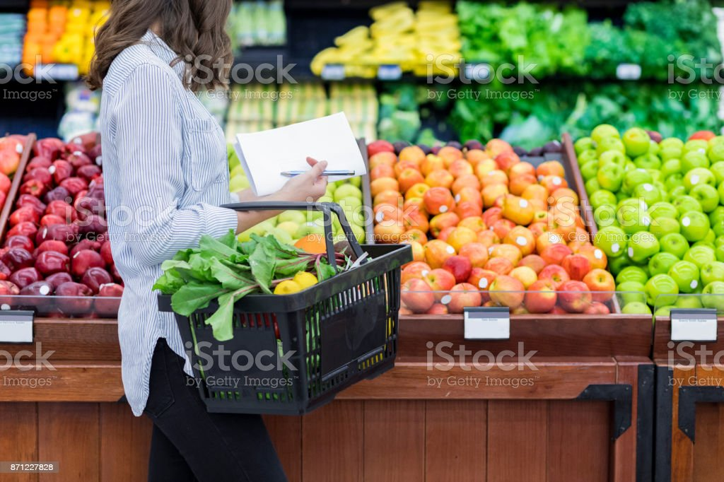 Unrecognizable woman shops for produce in supermarket stock photo