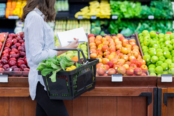 unrecognizable woman shops for produce in supermarket - shopping stock photos and pictures