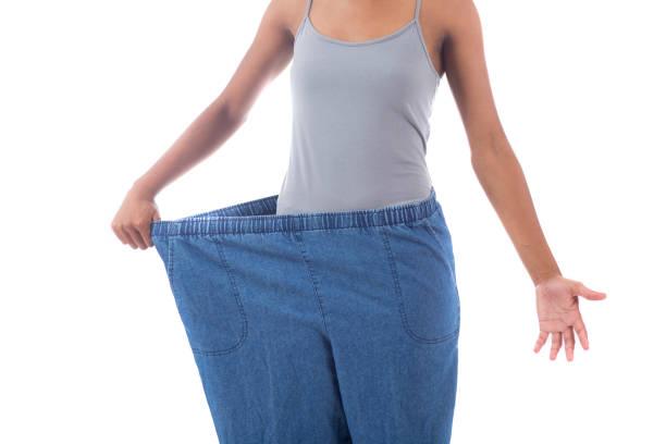 nicht erkennbare frau zeigt ihren gewichtsverlust - damen sporthose übergröße stock-fotos und bilder