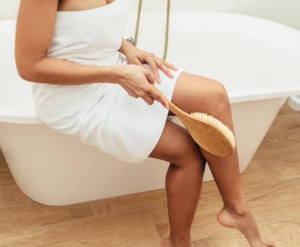 unerkennbare frau, die auf einem bad sitzt, in ein handtuch gehüllt und die haut auf einem bein mit holzbürste schrubbt - peeling bürste stock-fotos und bilder