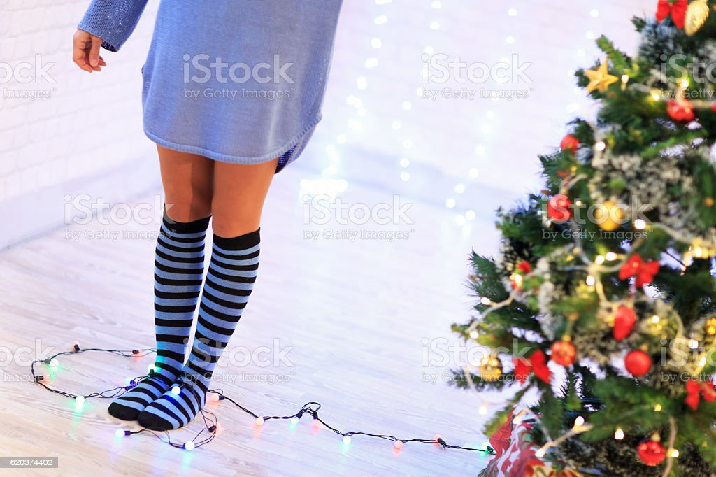 Unrecognizable woman standing shoeless next to christmas tree foto de stock royalty-free