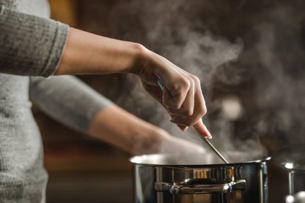 unrecognizable woman stirring soup in a saucepan while making lunch. - caçarola imagens e fotografias de stock