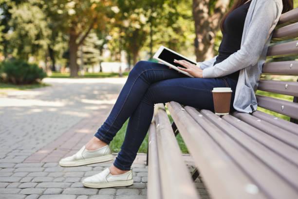 Femme méconnaissable, tapant sur la tablette à l'extérieur - Photo