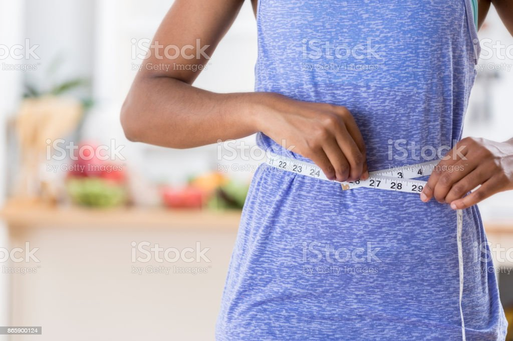 Unrecognizable woman uses measuring tape on waist stock photo