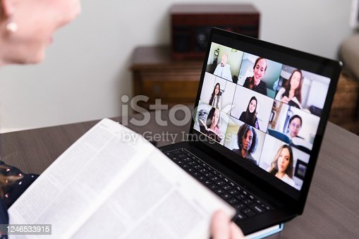 An unrecognizable woman uses her laptop at home to video conference with her friends for their monthly book club.