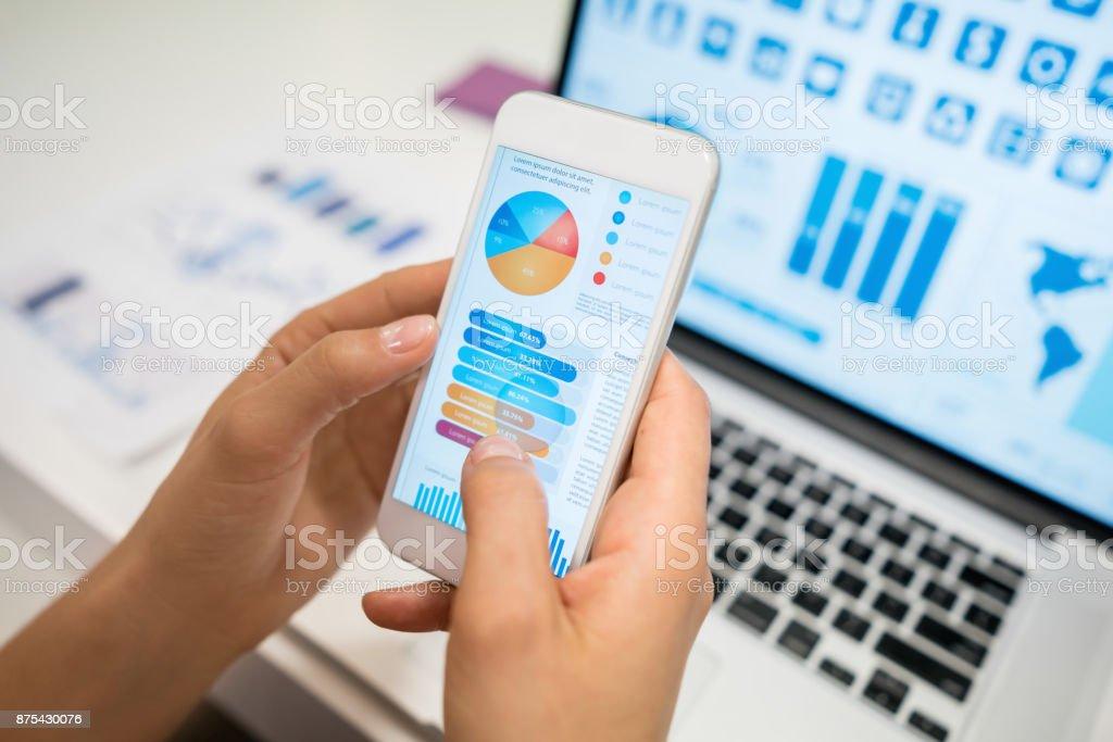 Nicht erkennbare Frau mit einer app Blick auf Statistiken – Foto