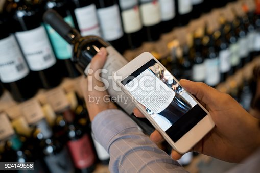 istock Unrecognizable woman using an application on smartphone to read more about the wine 924149556