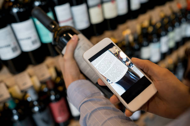Unrecognizable woman using an application on smartphone to read more about the wine stock photo