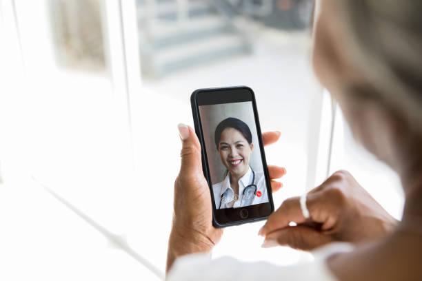 chats de video de mujer irreconocibles con el médico - telehealth fotografías e imágenes de stock