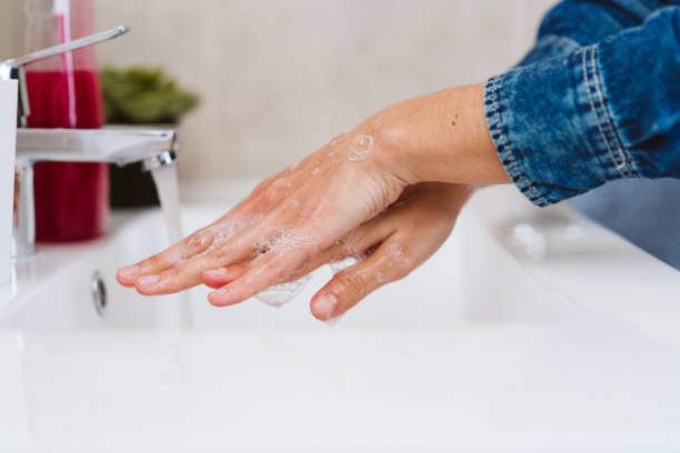 unrecognizable woman washing hands on a sink with soap. Coronavirus covid-19 concept stock photo