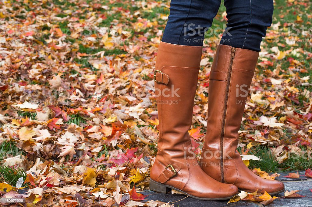Unrecognizable woman wearing brown boot  and standing on foliage stock photo