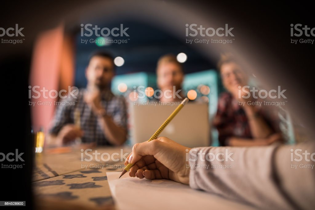 Unrecognizable woman writing on a piece of paper during the meeting. royalty-free stock photo