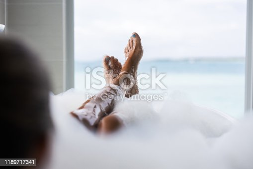 Unrecognizable woman's feet relaxing on a bathtub during bubble bath.