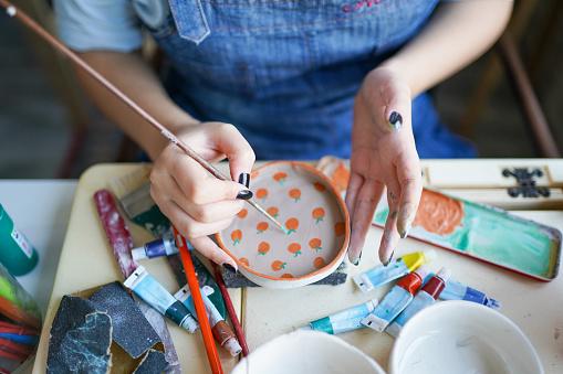 unrecognizable woman's hand paints ceramics