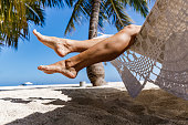 Unrecognizable woman's legs during serene moment on a hammock at the beach. Copy space.