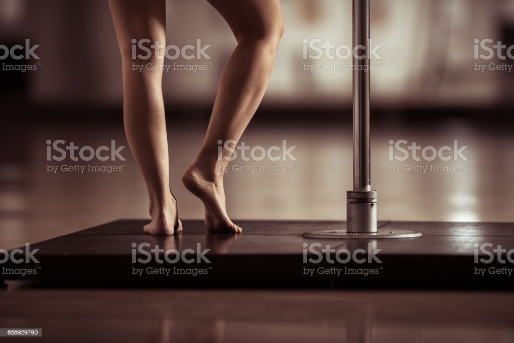 Unrecognizable woman's legs next to dancing pole. stock photo
