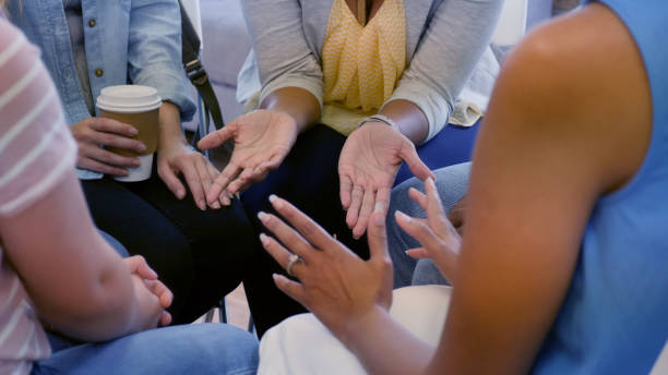 Unrecognizable women gesturing during group therapy stock photo