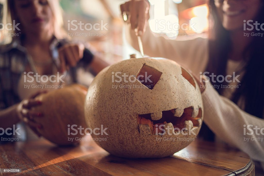Unrecognizable women making Jack O' Lantern for Halloween. stock photo