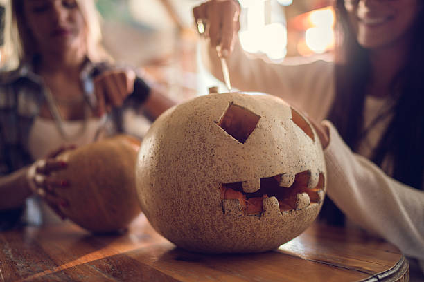 Unrecognizable women making Jack O' Lantern for Halloween. – Foto
