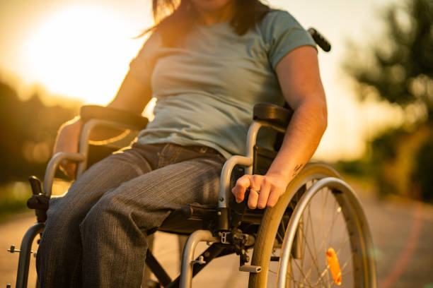 Unrecognizable women on a wheelchair at sunset Close up unrecognizable women on a wheelchair at sunset paraplegic stock pictures, royalty-free photos & images