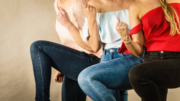 Unrecognizable women presenting outfit Three unrecognizable women having fashionable outfits, blue jeans and colorful shirts. Fashion and clothing concept. skinny jeans stock pictures, royalty-free photos & images