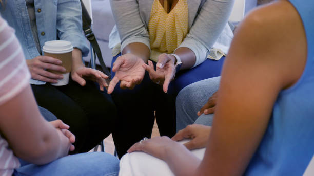 Unrecognizable women sitting together for group therapy An unrecognizable group of women drink coffee and sit in a circle together for group therapy.  One woman gestures. group therapy stock pictures, royalty-free photos & images