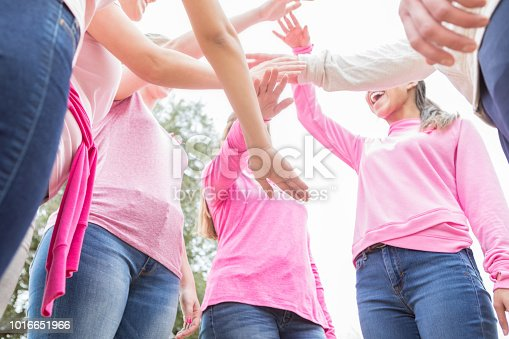 Group of women stand in a circle with their hands together in unity during a cancer awareness fundraising event.