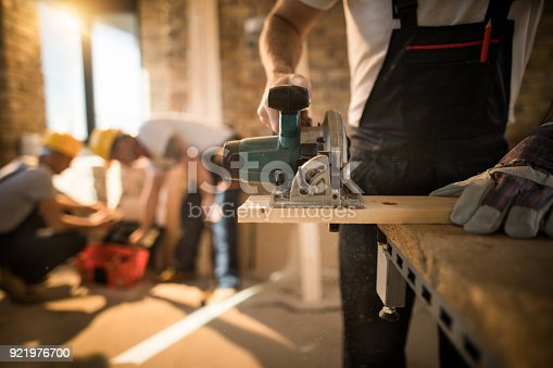 istock Unrecognizable worker cutting plank with circular saw at construction site. 921976700