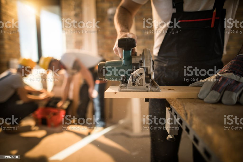 Unrecognizable worker cutting plank with circular saw at construction site. stock photo