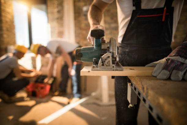 unrecognizable worker cutting plank with circular saw at construction site. - builders stock photos and pictures