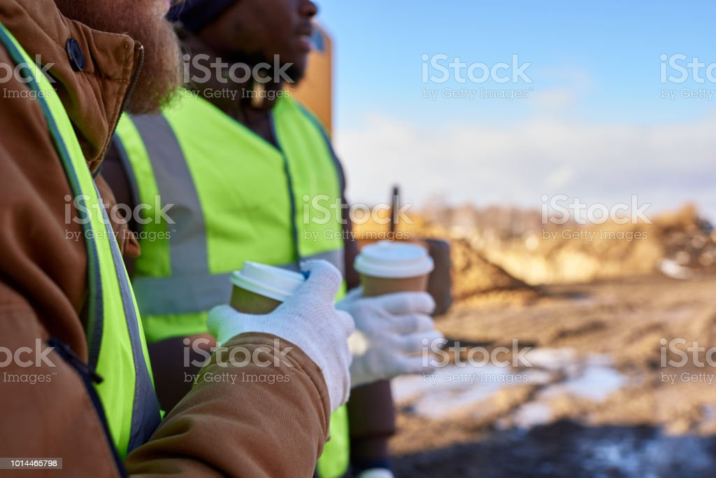 Unrecognizable Workers on Coffee Break Closeup of two workers, one African-American, drinking coffee and chatting next to heavy industrial truck on worksite, copy space Abstract Stock Photo