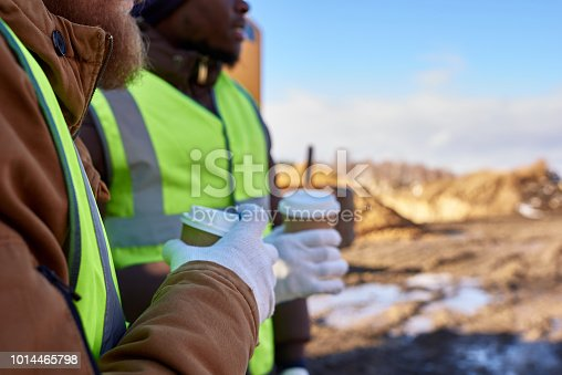 Closeup of two workers, one African-American, drinking coffee and chatting next to heavy industrial truck on worksite, copy space