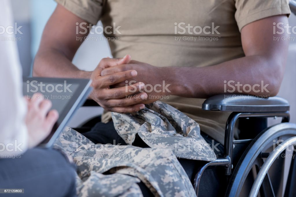Unrecognizable wounded military officer talks to therapist stock photo