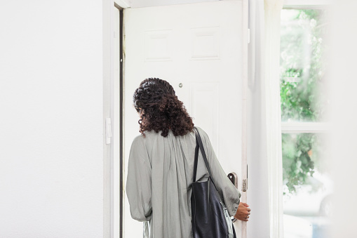The unrecognizable young adult woman leaves her house carrying a purse.  She is leaving through the front door.