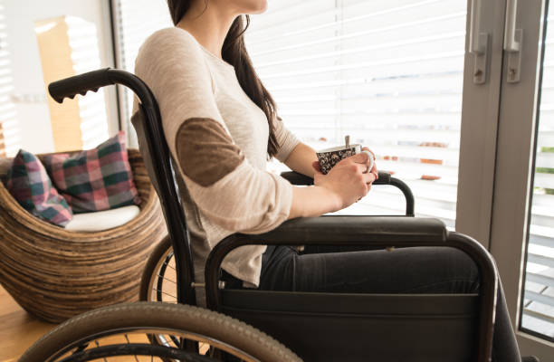 Unrecognizable young disabled woman in wheelchair at home. - foto de stock