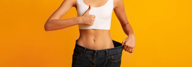 Unrecognizable Young Lady In Oversize Pants Gesturing Thumbs-Up, Studio Shot Unrecognizable Young Lady In Oversize Pants Gesturing Thums-Up On Yellow Background. Slimming And Weight Loss. Crop, Panorama, Copy Space liposuction stock pictures, royalty-free photos & images